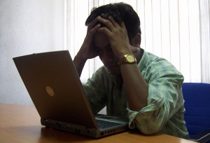 Frustrated man at a laptop