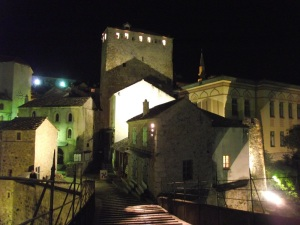 View of buildings lit up from the top of Mostar's old bridge at night