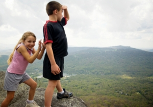 Girl pretends to push brother off a cliff